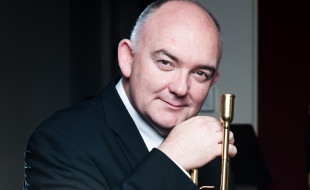 Image of James Morrison holding a trumpet and smiling into the camera
