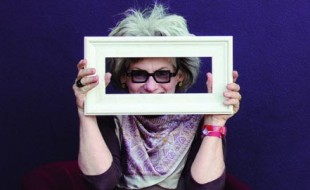 Image of Margi Brown Ash holding a picture frame and smiling