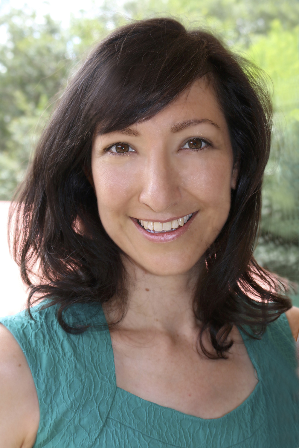 Professional headshot of Hana. She has dark shoulder length hair and is wearing a green top. She is outdoors and smiling.