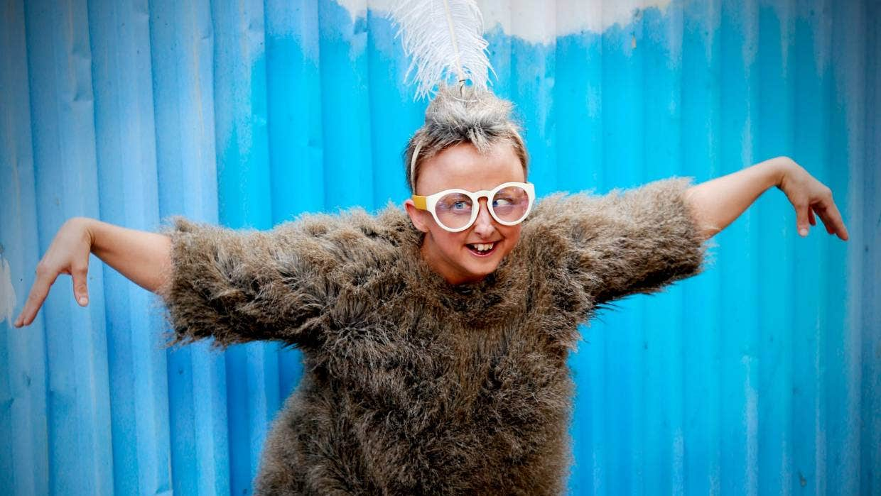 Sarah standing in front of a bright blue background, leaning forward with her arms out wide. She is wearing a furry shirt, white framed glasses and feathers on top of her head.