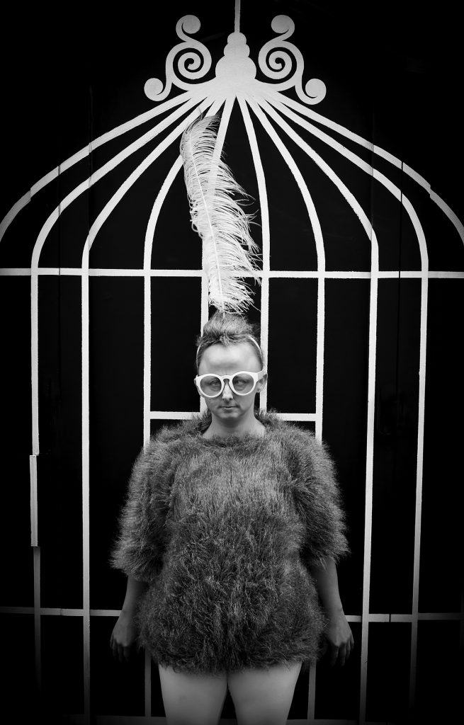 Sarah in costume as Koo Koo the Bird Girl. She is wearing a feathered vest, thick white glasses and a headband with feathers. She is standing in front of a birdcage.