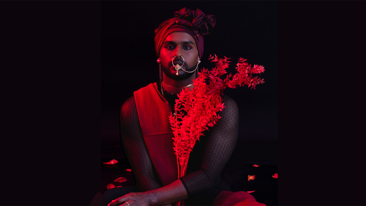 An image washed in red. A person pictured from the waist up looks directly at the camera, wearing a wrapped head scarf. they have a large nose piercing attached by a chain to their ear, and are holding branches of foliage.