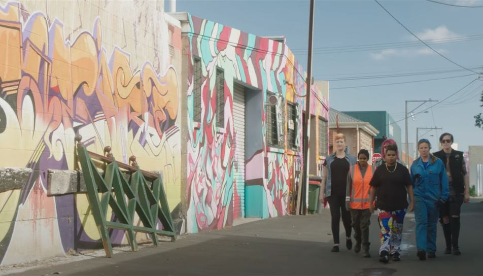 A group of women walk down a laneway. There is brightly coloured graffiti on the wall beside them.
