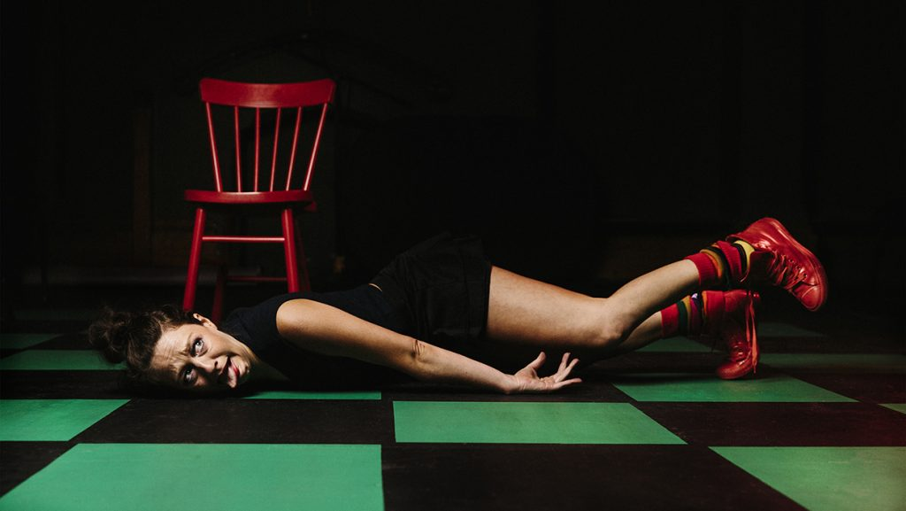Andi photographed while performing. She is lying down on a green and black tiled floor, pulling a face with her tongue poked out. There is a bright red wooden chair behind her.