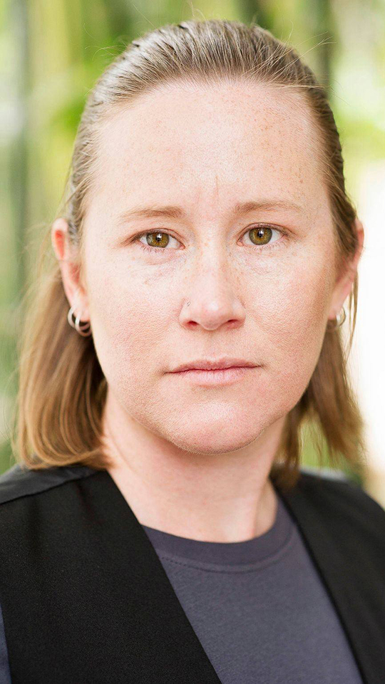 A headshot of a person looking directly at the camera. The have blonde hair pulled back off their face and are wearing a grey top and black jacket.