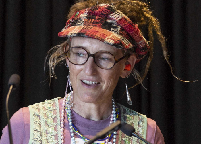Larissa speaking into two small microphones. She is wearing a tartan visor and reading glasses. Her hair is styled in dreadlocks worn high on her head.