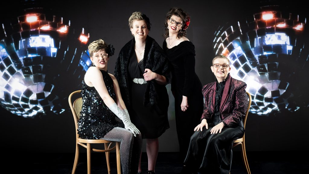 The Sisters of Invention members. Michelle and Caroline are seated on wooden chairs either side of Aimme and Annika who are standing. There are disco balls superimposed in the background.