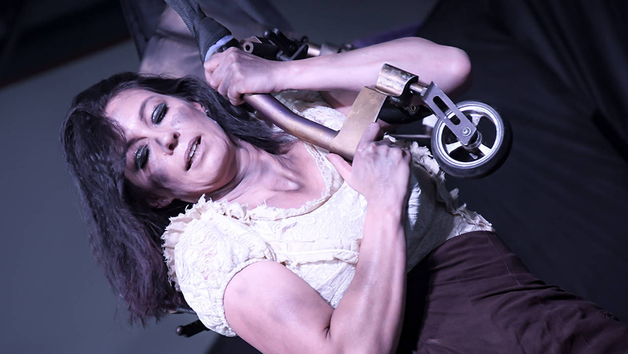 Lauren pictured mid-performance in close up. She is holding tightly to the leg of her wheel chair asn looking towards the ground. She has dark eye make up on and her dark hair is out.
