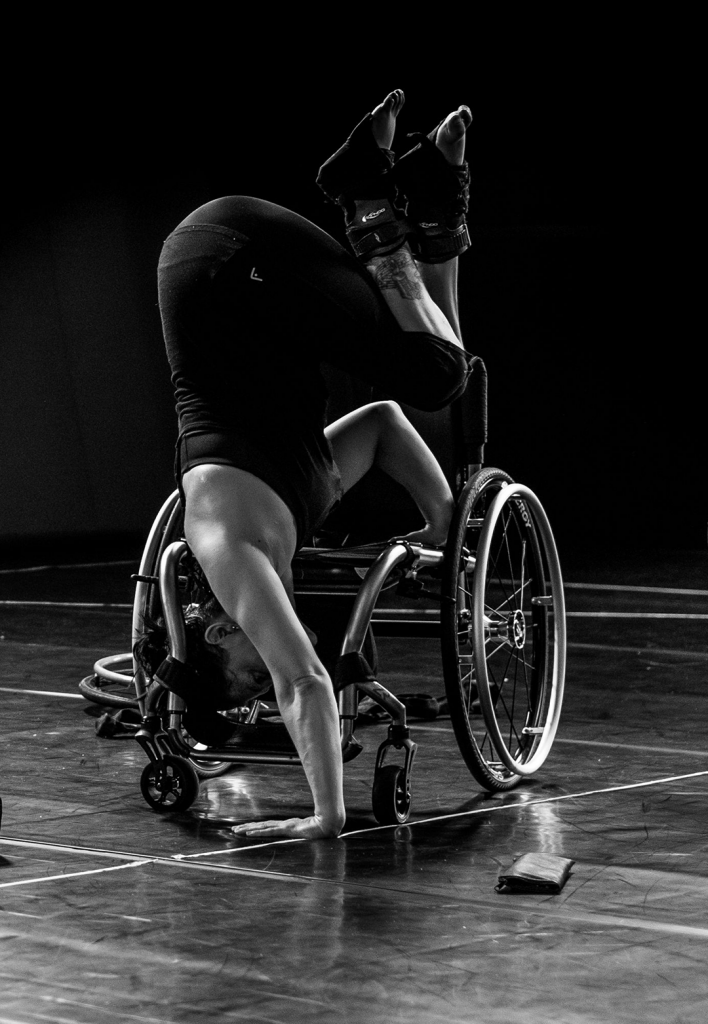 A black and white image of Lauren in a handstand pose. She has one palm on teh floor and one on her wheelchair behind her.