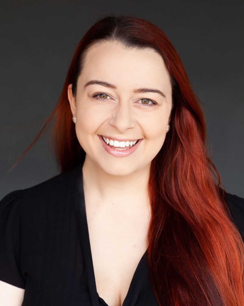 A professional headshot of Madeleine. She has long red hair and is wearing a black top and smiling.