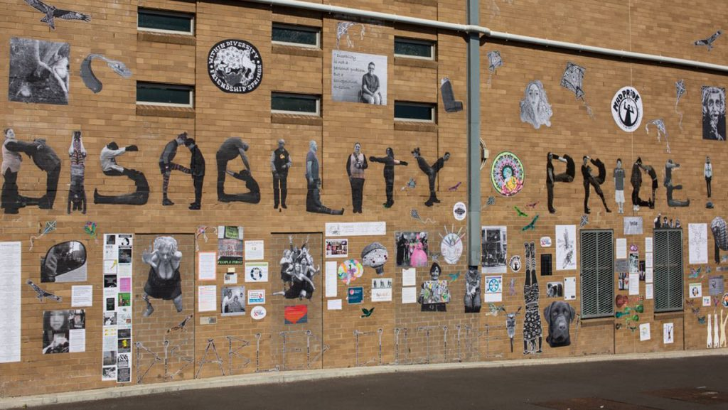 A brown brick wall with the words Disability Pride spelled out across it
