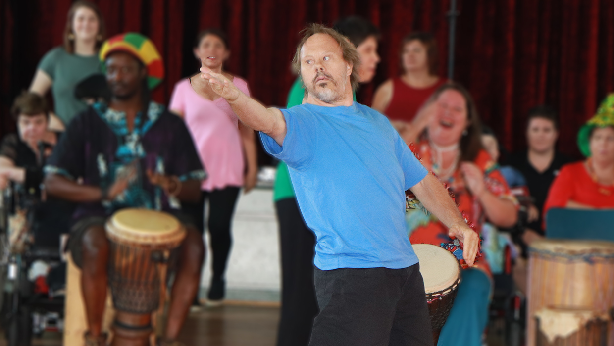 A man standing with one hand held out gesturing to the audience. He is wearing a blue t-shirt and dark pants. There are other performers out of focus in the background.