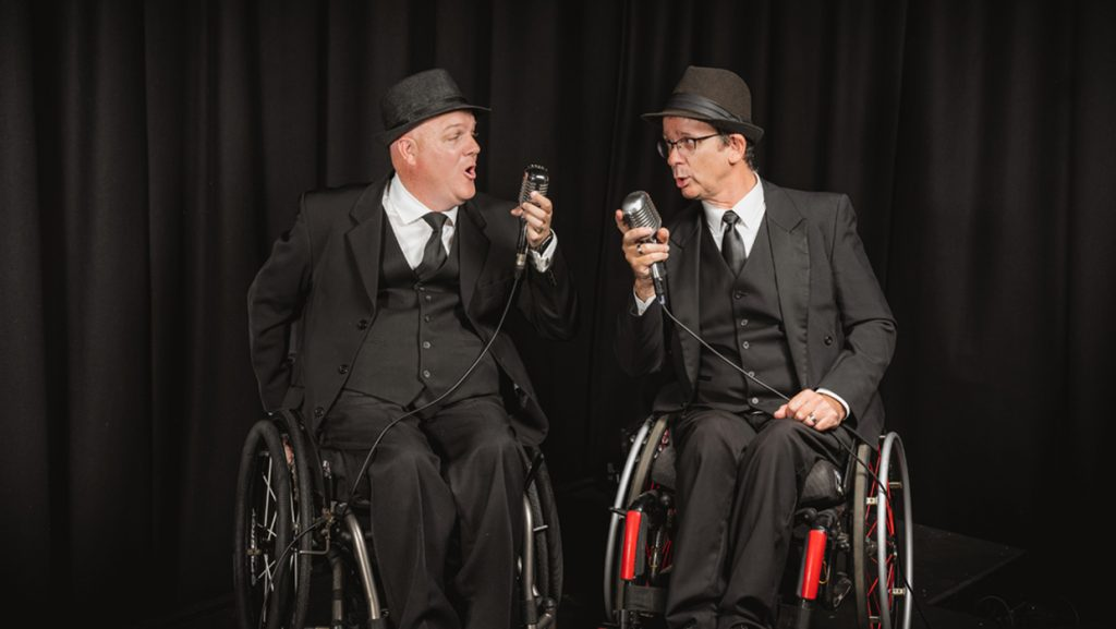 Two men seated in wheelchair wearing black three piece suits and hats. Each is holding a vintage microphone and looking towards one another singing.