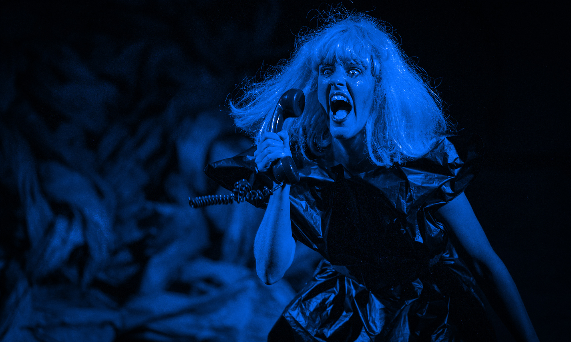 A blue washed image of Andi Snelling mid-performance. She is wearing a blonde wig and holding a phone up to her ear.