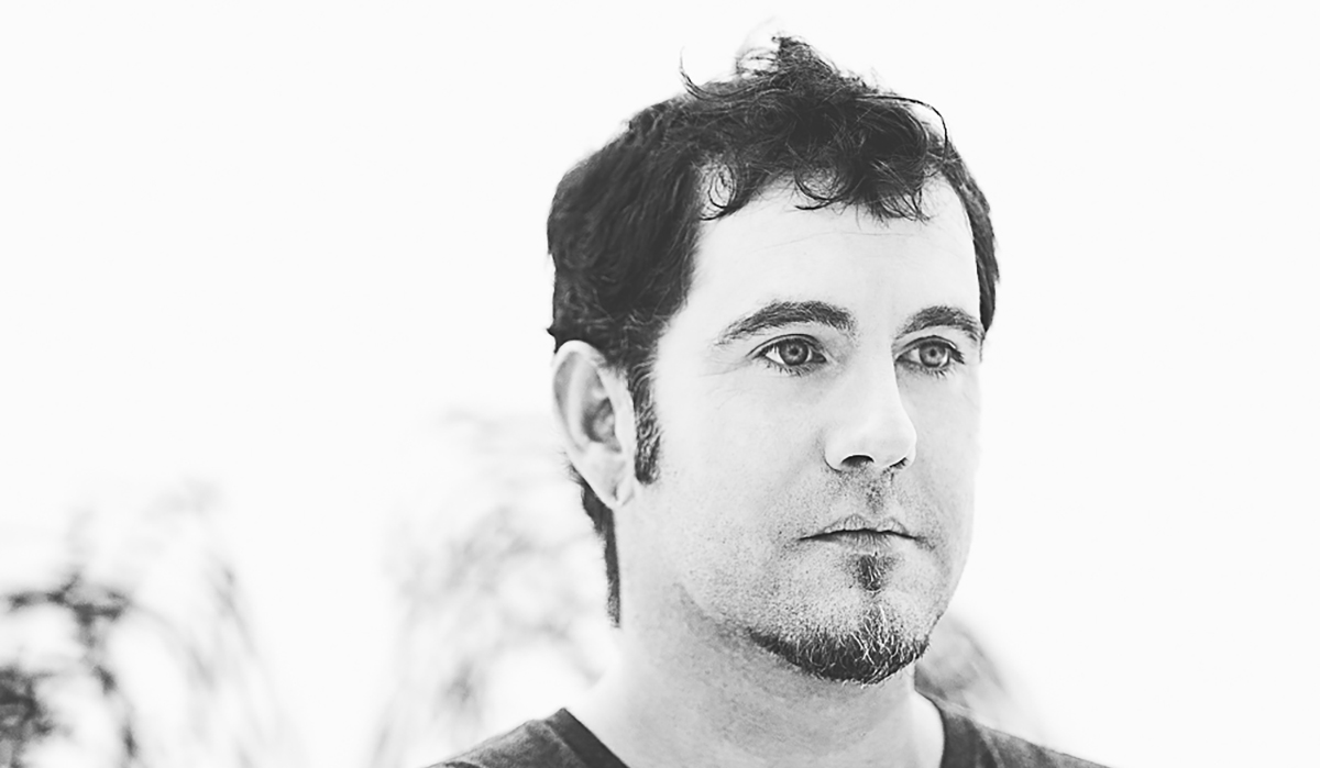 A light, black and white headshot of Jeremy. He has short dark hair and is looking away from the camera.