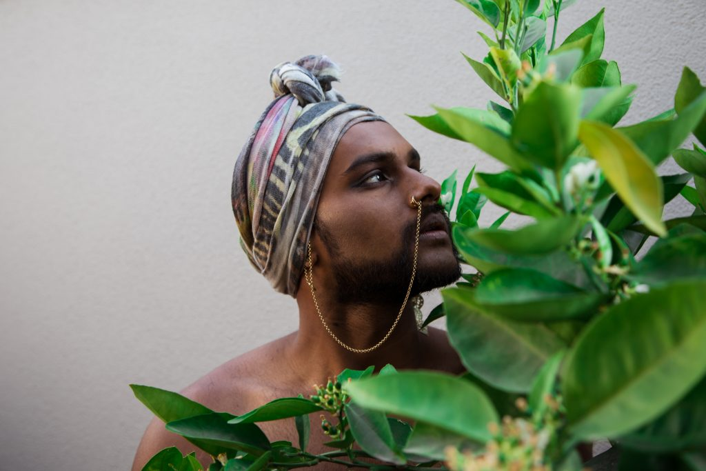 Naavikaran pictured in focus behind green foliage. They are wearing a patterned head scarf wrapped around their head and have a gold chain linking a nose ring to their ear.