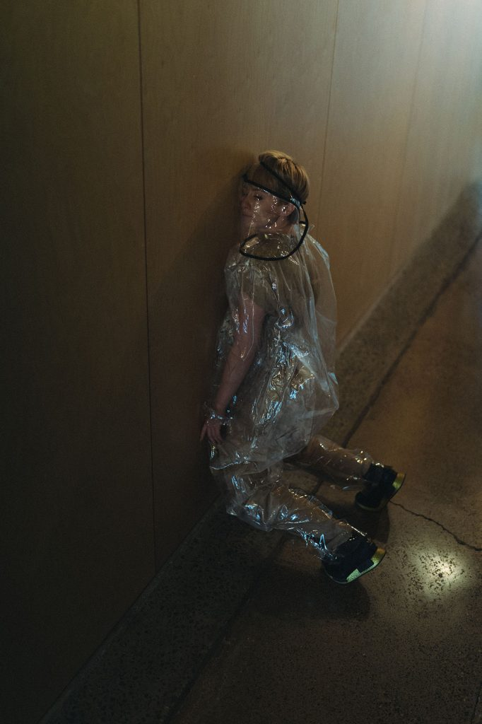 Ruby wearing a see-through plastic outfit and mask. She is leaning her cheek against a wall in an empty hallway.