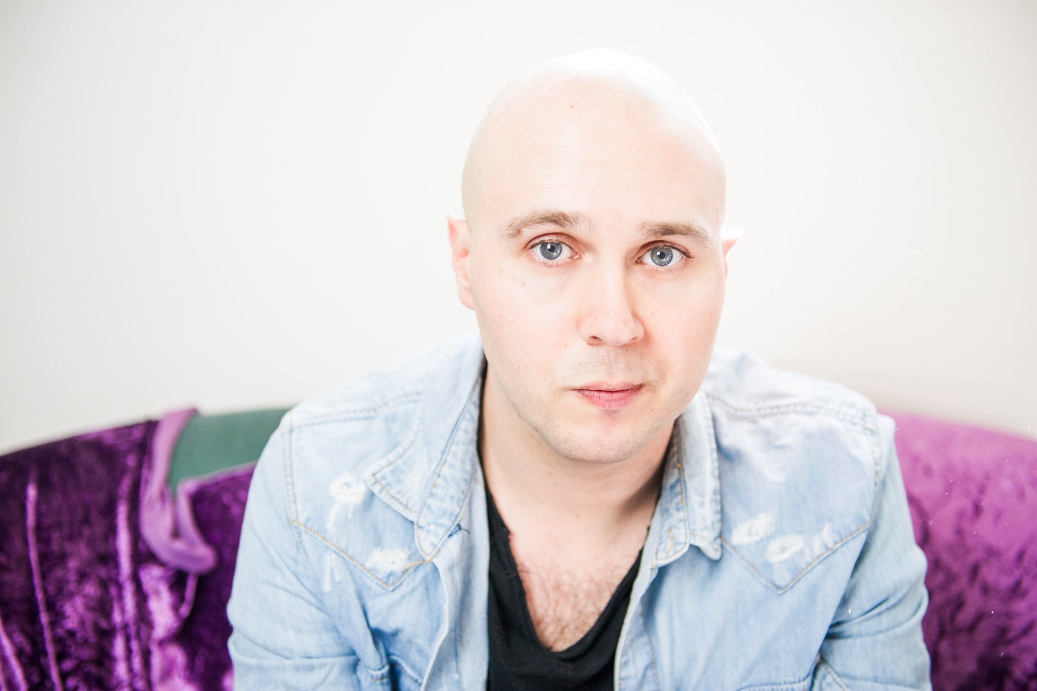 A headshot of Alex Edwards looking directly at the camera. He has a shaved head and is wearing a light denim shirt.