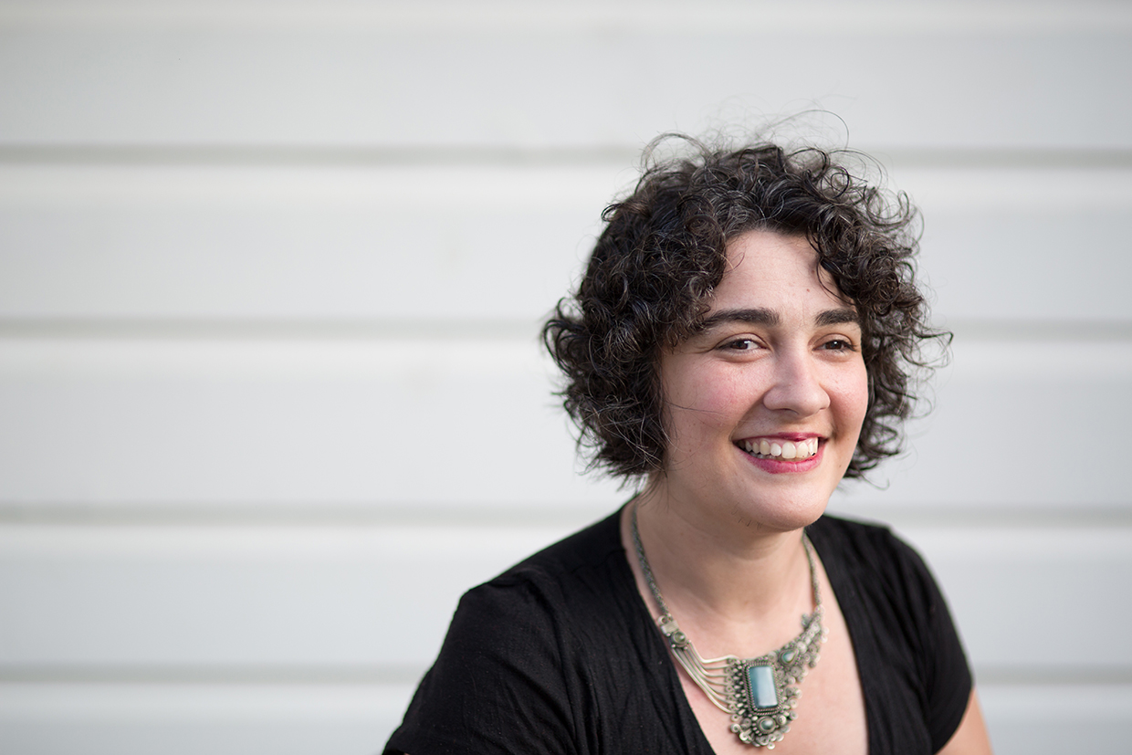 Alex pictured slightly off-centre, in front of a white panelled wall. She has dark curly hair and she is smiling.